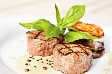 Grilled veal medallions with eggplants, tomatoes and basil